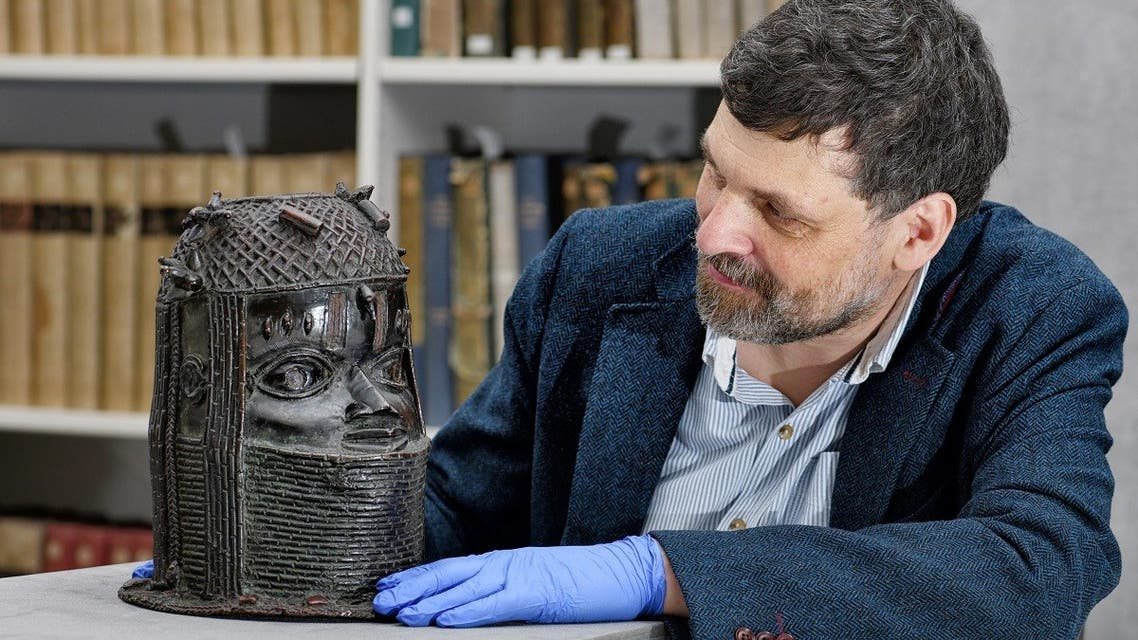 Neil Curtis, Head of Museums and Special collections is seen with one of the Benin bronze depicting the Oba of Benin at The Sir Duncan Rice Library, the University of Aberdeen, in Aberdeen, Scotland, Britain, on March 17, 2021. (Reuters)