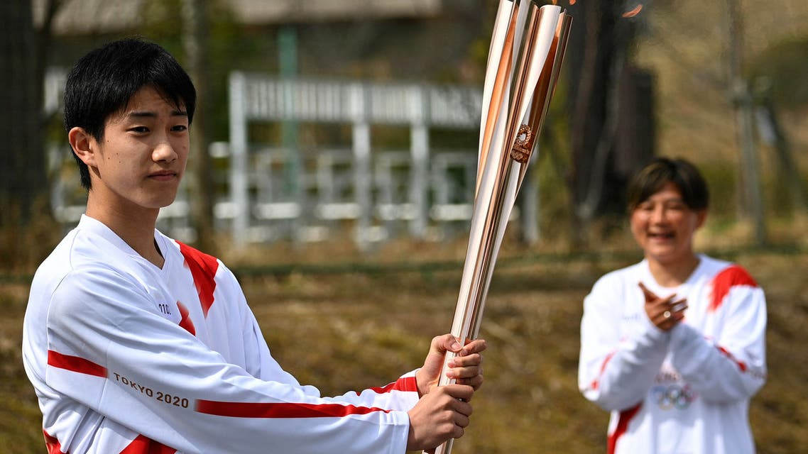 Japanese high school student Asato Owada carries the Olympic torch ahead of the Tokyo 2020 Olympic Games during the torch relay grand start outside the J-Village National Training Centre in the town of Naraha, Fukushima Prefecture on March 25, 2021. (File photo: AFP)