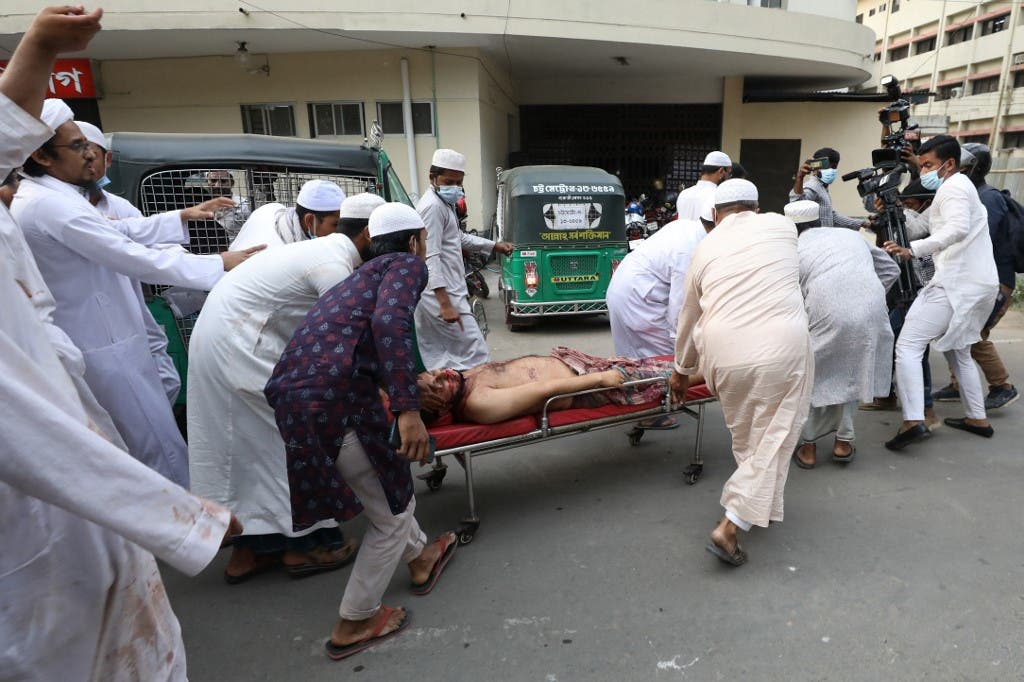 Activists of the Hifazat-e Islam group carry an injured activist on a stretcher outside the Chittagong medical college hospital in Chittagong on March 26, 2021 following clashes with police during a demonstration against Indian Prime minister Narendra Modi's visit to Bangladesh. (AFP)