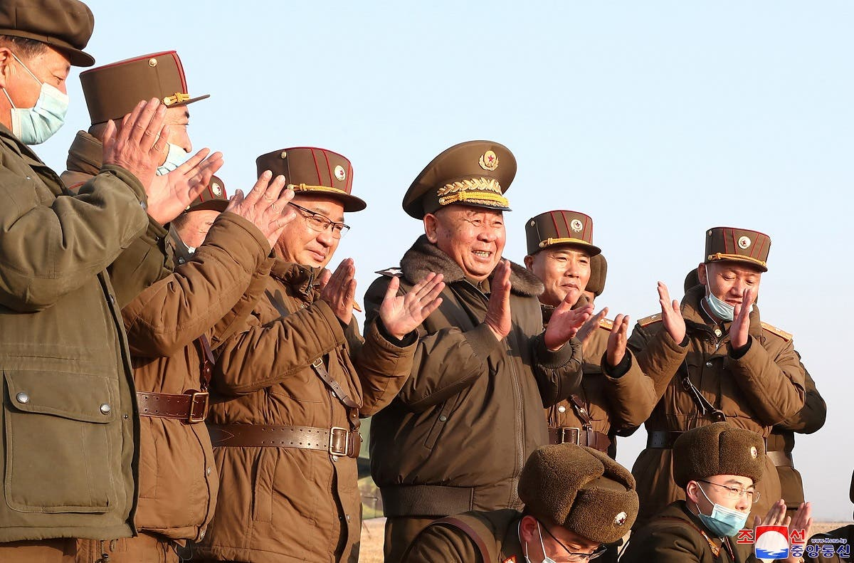 Ri Pyong Chol, the senior leader who is overseeing the test, and other military officials applaud after the launch of a newly developed new-type tactical guided projectile on March 25, 2021. (Reuters)