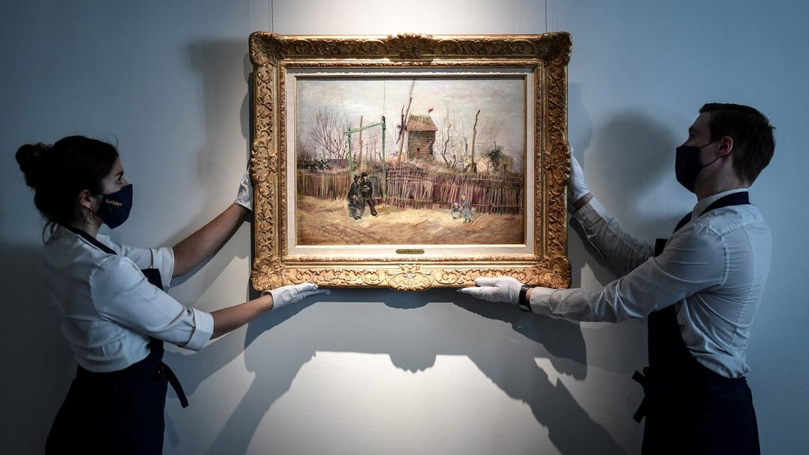 FILE PHOTO: Sotheby's Paris employees pose with the 1887 painting of a Paris street scene Scene de rue a Montmartre by Dutch painter Vincent Van Gogh which will be presented to the public for the first time after spending more than a century behind closed doors in the private collection of a French family, France, February 24, 2021. REUTERS/Christian Hartmann/File Photo