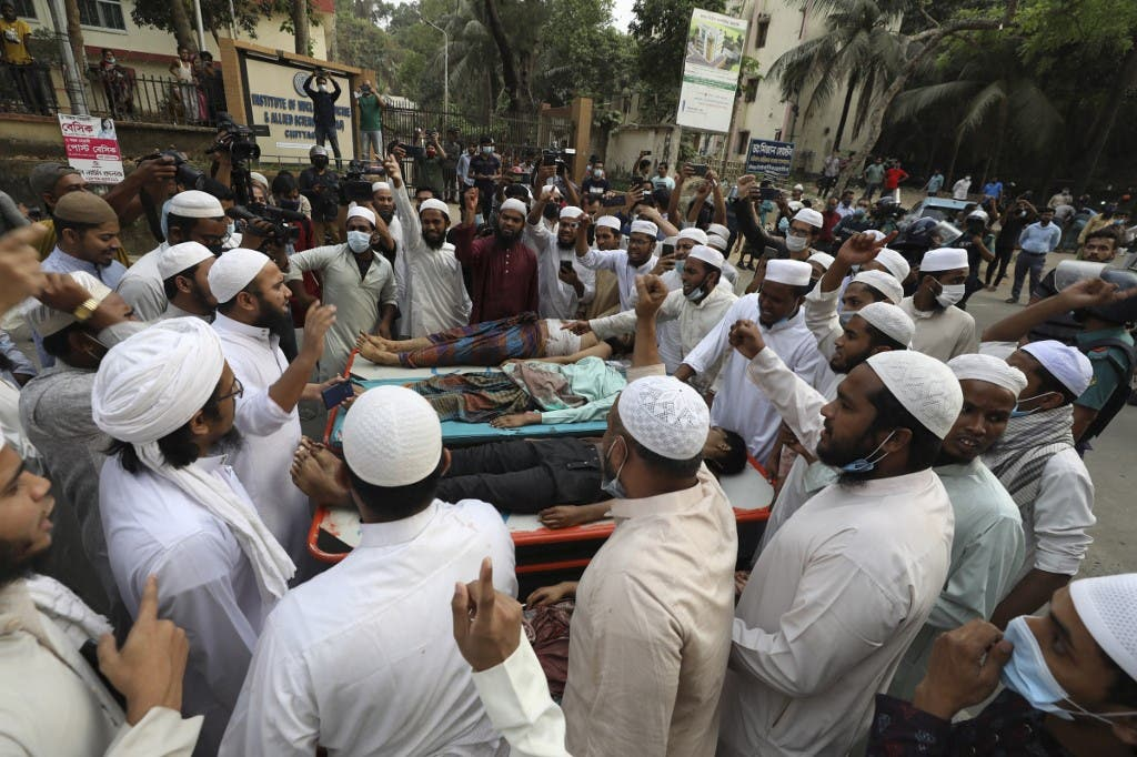 Activists of the Hifazat-e Islam group shout slogans next to the dead bodies of other activists outside the Chittagong medical college hospital in Chittagong on March 26, 2021 following clashes with police during a demonstration against Indian Prime minister Narendra Modi's visit to Bangladesh. (AFP)