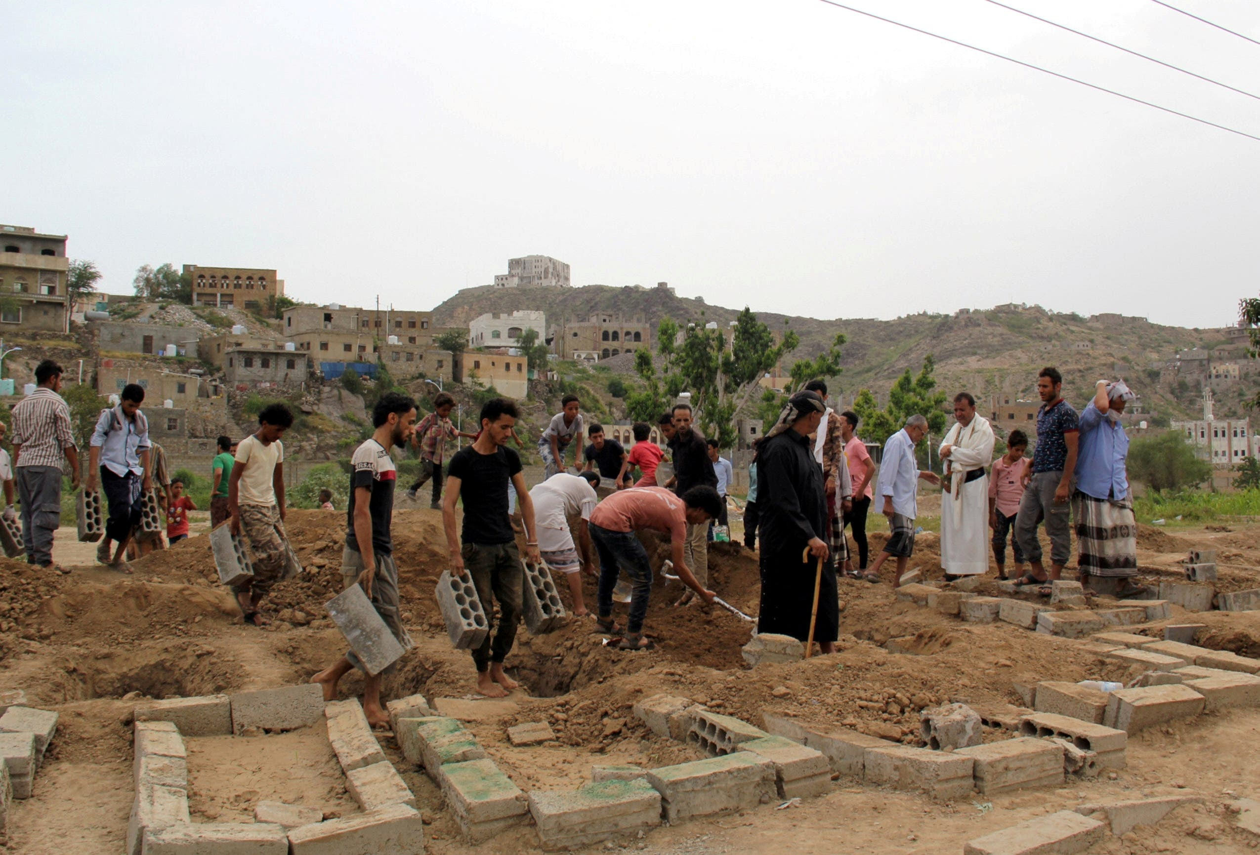 People arrange a grave after a burial at a cemetery where victims of the coronavirus disease (COVID-19) are buried in Taiz, Yemen June 24, 2020. Picture taken June 24, 2020. (Reuters)