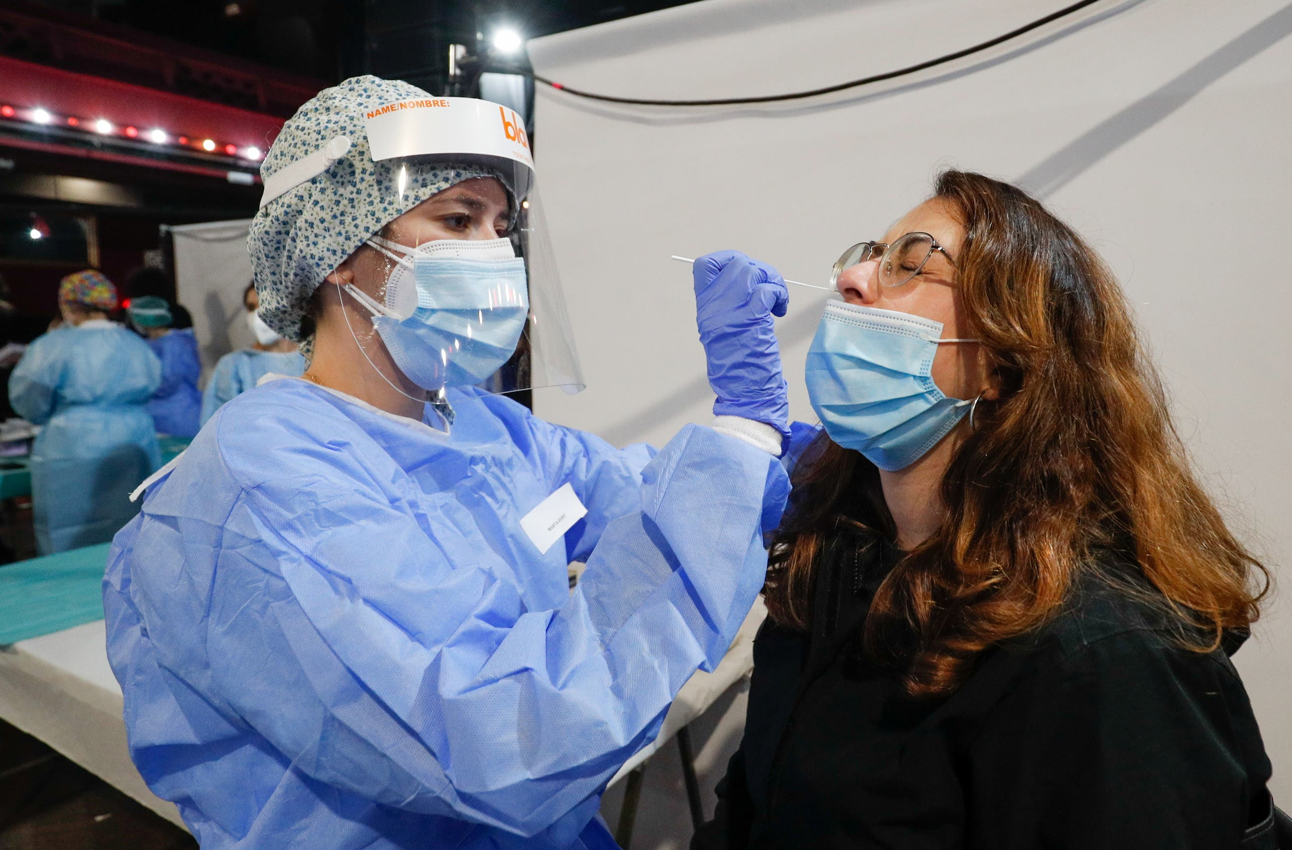 A healthcare worker collects a swab sample from a woman, before a concert of Love of Lesbian that will take place this afternoon with 5,000 spectators at the Palau Sant Jordi, amid the coronavirus disease (COVID-19) pandemic, in Barcelona, Spain, March 27, 2021. (Reuters)