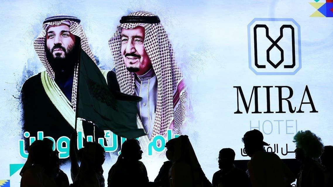 People walk past a poster of Saudi Arabia's King Salman bin Abdulaziz Al Saud and Crown Prince Mohammed bin Salman as they celebrate Saudi Arabia's 90th annual National Day. (Reuters)