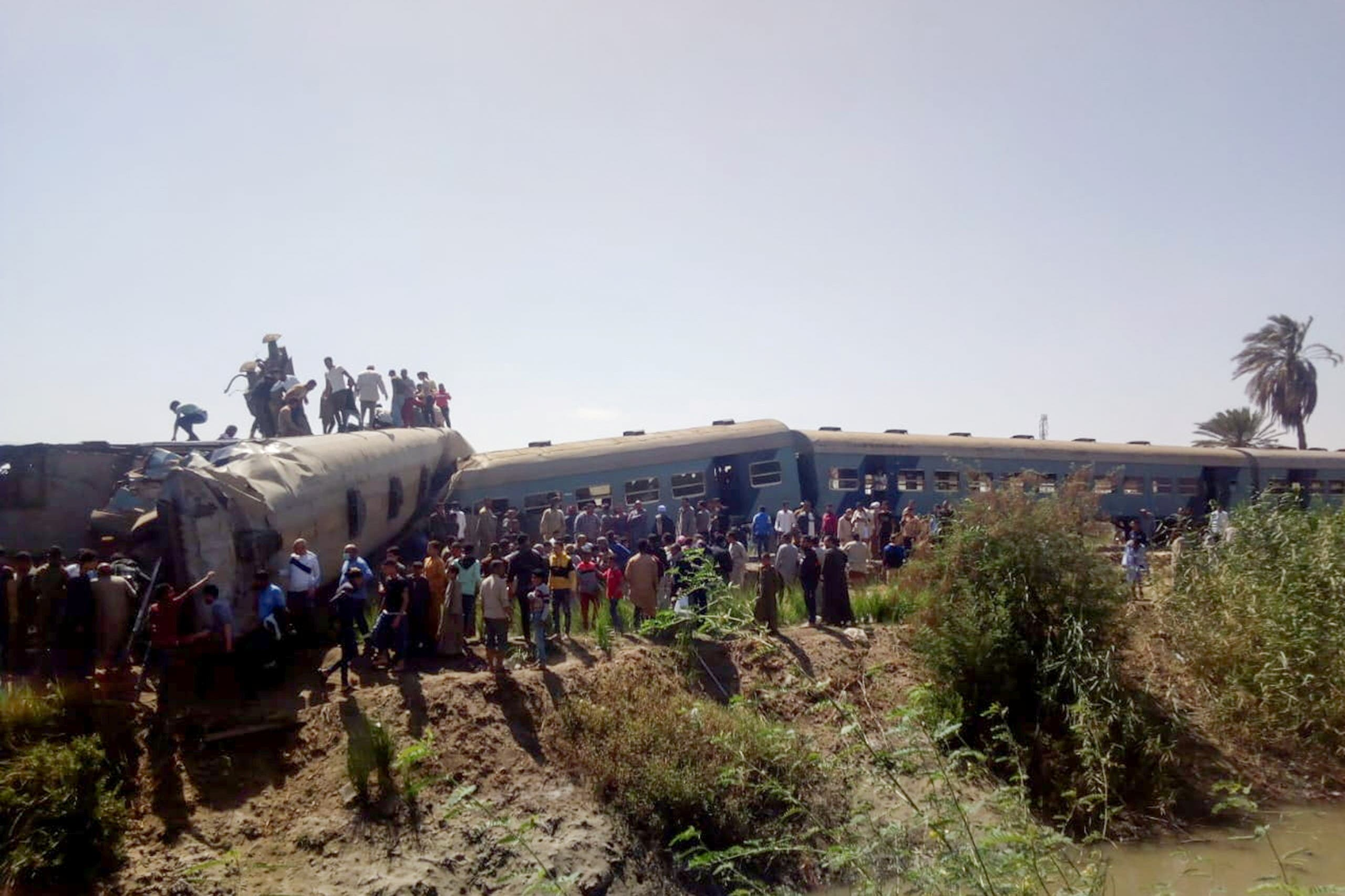 People inspect the damage after two trains have collided near the city of Sohag. (Reuters)