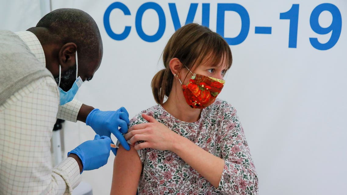 A woman receives a dose of COVID-19 vaccine in a vaccination centre at Newmarket Racecourse, amid the coronavirus disease outbreak in Newmarket, Britain March 26, 2021. REUTERS/Andrew Couldridge