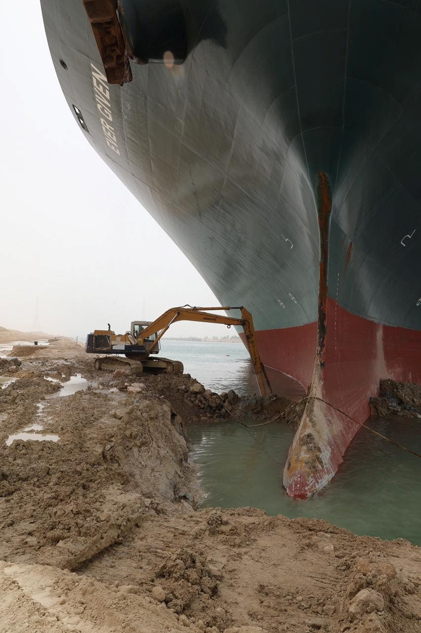 An excavator attempts to free stranded container ship Ever Given, one of the world's largest container ships, after it ran aground, in Suez Canal, Egypt March 25, 2021. (Suez Canal Authority/Handout via Reuters)