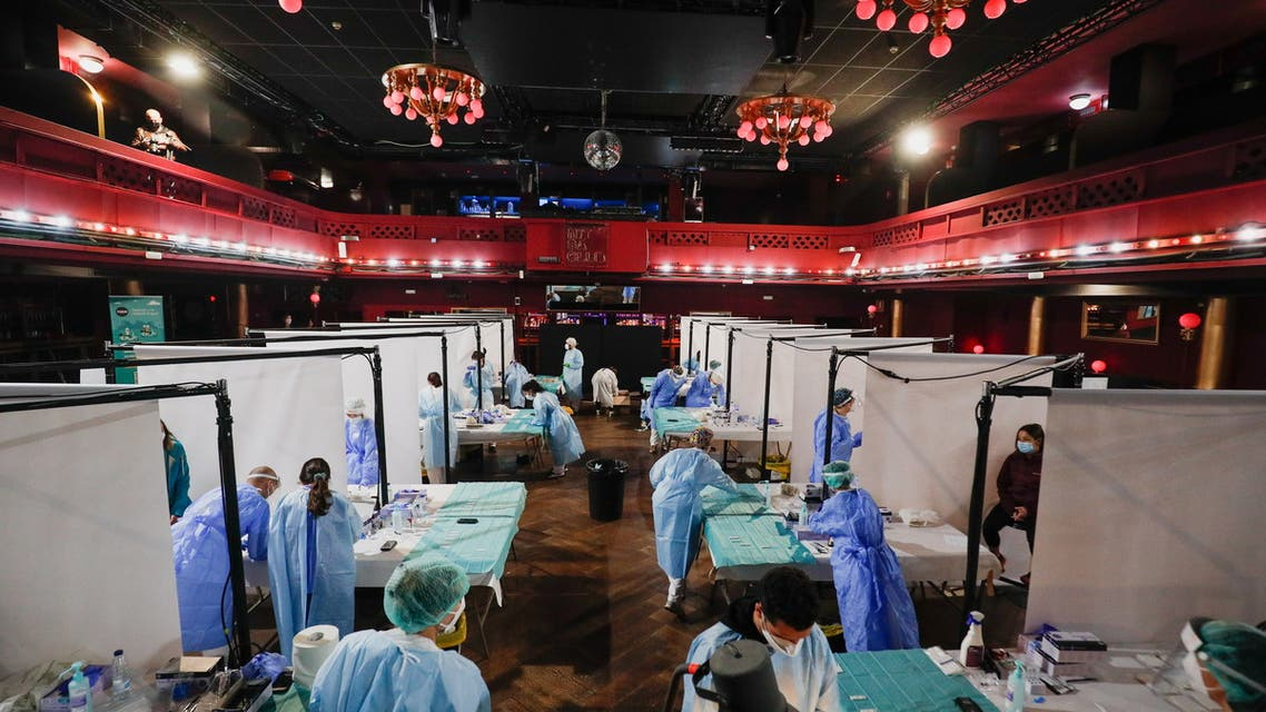 Healthcare workers prepare to collect swab samples from people, before a concert of Love of Lesbian that will take place this afternoon with 5,000 spectators at the Palau Sant Jordi, amid the coronavirus disease (COVID-19) pandemic, in Barcelona, Spain, March 27, 2021. (Reuters)