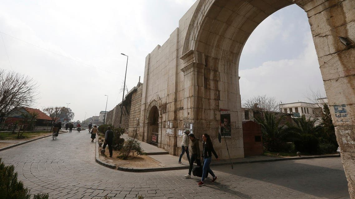 Syrians commute through Bab Sharqi (The Eastern Gate), one of the capital city's historic gates in Damascus' old town, on March 2, 2021. (AFP)