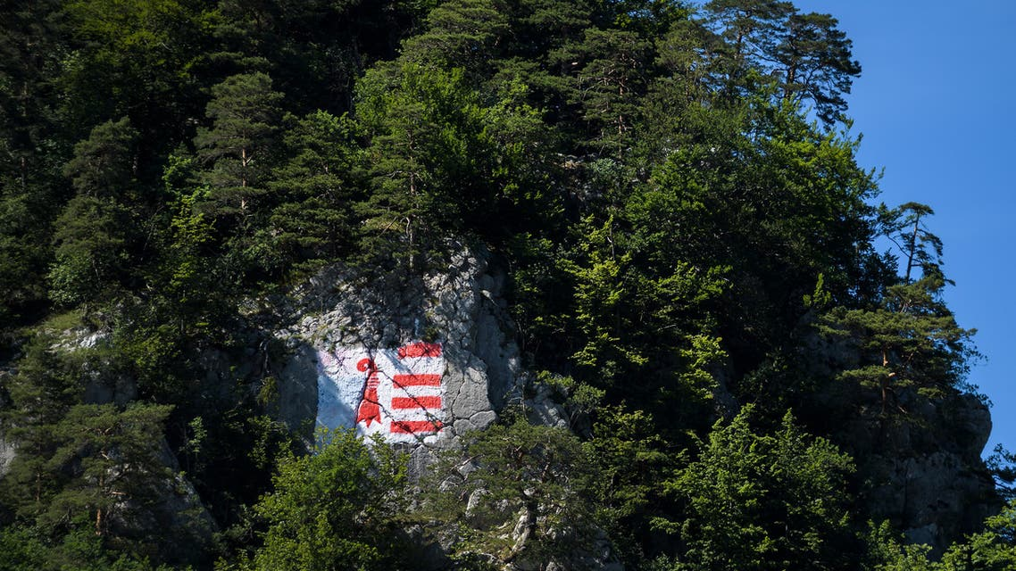 A picture taken on June 18, 2017 in Moutier, northern Switzerland shows a flag of Jura canton painted on the mountain overlooking the village during an historical anticipated vote. Moutier vote for the fifth time in 42 years on whether to remain part of German-speaking canton Bern or whether to join primarily French-speaking canton Jura. The vote is such a major and sensitive event that the federal government has decided to send in observers. (File photo: AFP)