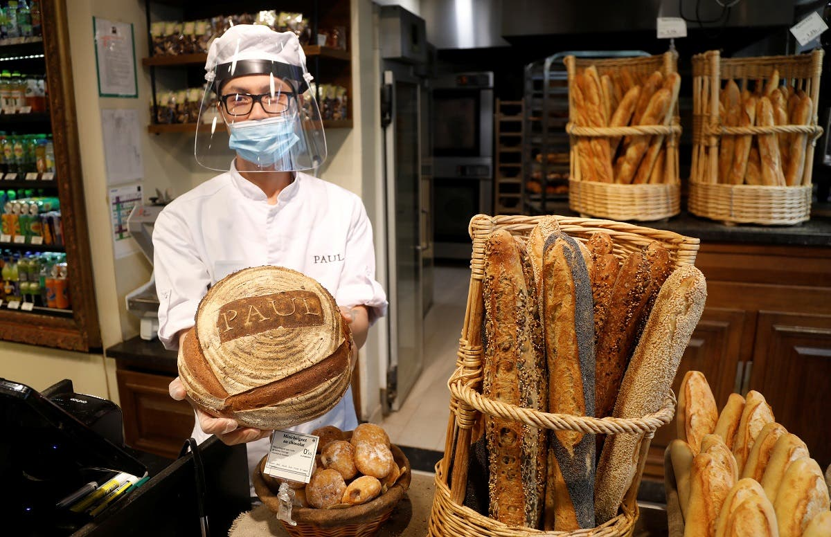 An employee, wearing a protective face mask and face shield, poses with bread and French baguettes at Paul bakery during the outbreak of the coronavirus disease (COVID-19) in Paris, France, May 5, 2020.  (Reuters)