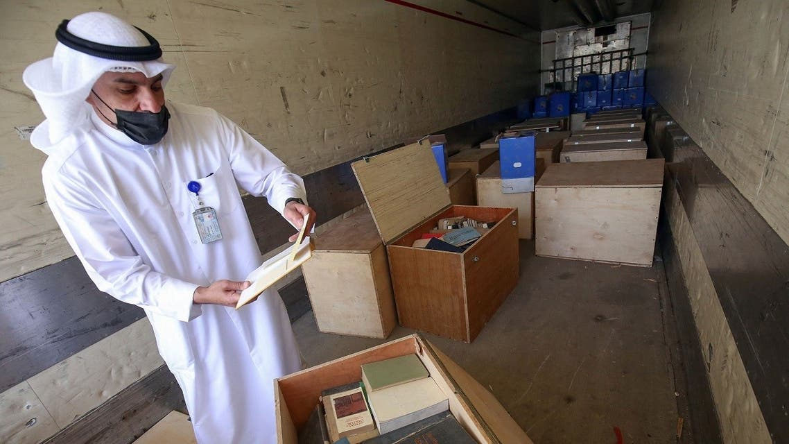 Employee at the Kuwaiti Information Ministry Essam al-Said inspects boxes in the back of a truck containing Kuwaiti archives seized during the Iraqi invasion of the Gulf emirate in 1990, after their restitution by Iraqi authorities in Kuwait City, on March 28, 2021. (Yasser Al-Zayyat/AFP)