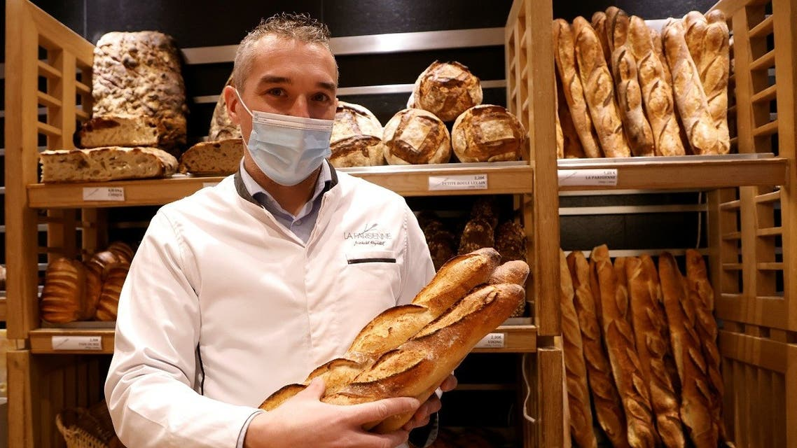 French baker Mickael Reydellet, wearing a protective face mask, poses with freshly-baked baguettes at La Parisienne bakery in Paris, France, February 17, 2021.  (Reuters)