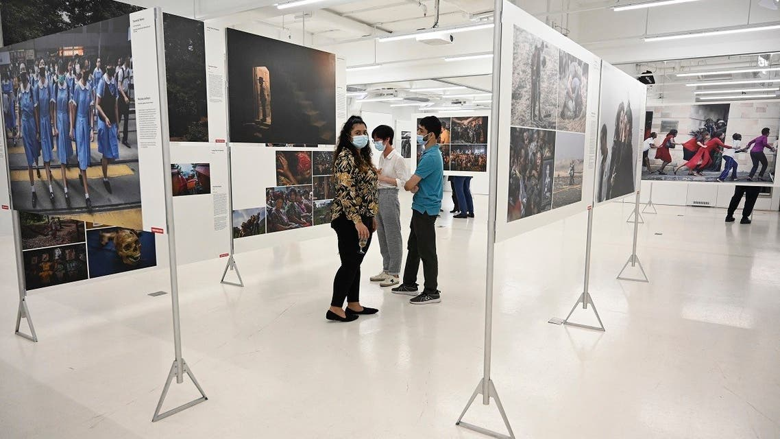 Guests look at photos from the World Press Photo exhibition in Hong Hong on March 28, 2021 as it opened at a new venue after a local university previously called off the exhibition featuring photos of the city's 2019 protests over security fears. (Peter Parks/AFP)