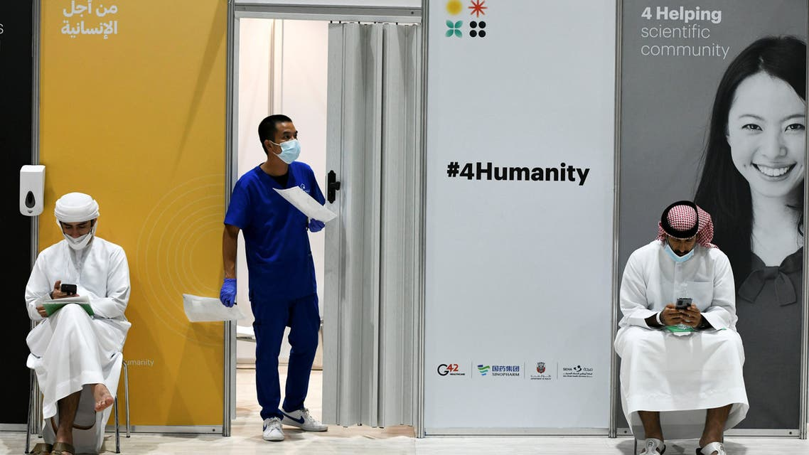 People wearing protective face masks use their mobiles as they wait for vaccine trials at Abu Dhabi National Exhibition Centre in Abu Dhabi, United Arab Emirates, October 6, 2020. Picture taken October 6, 2020. (File photo: Reuters)