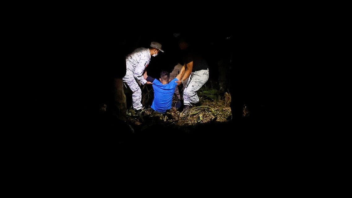 National Institute of Immigration agents and members of the National Guard detain two migrants from Central America after they were spotted with a large group on the motorway near Palenque, Chiapas, Mexico March 27, 2021. (Reuters/Carlos Jasso)
