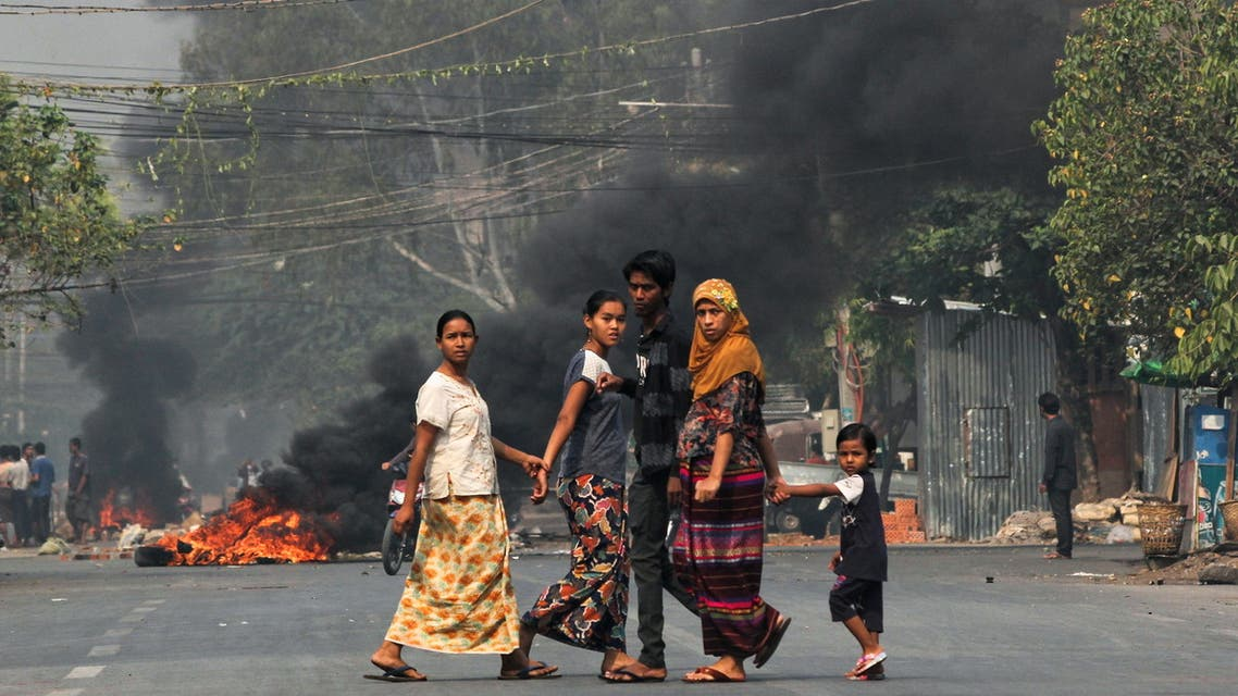 People walk on a street as barricades burn behind them during a protest against the military coup, in Mandalay, Myanmar March 27, 2021. (Reuters)