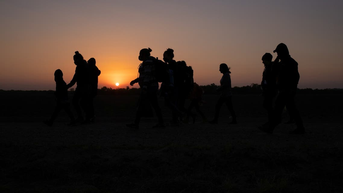 The sun rises as asylum-seeking migrants' families from Honduras and El Salvador walk towards the border wall after crossing the Rio Grande river into the United States from Mexico on a raft, in Penitas, Texas, US, March 26, 2021. (File photo: Reuters)