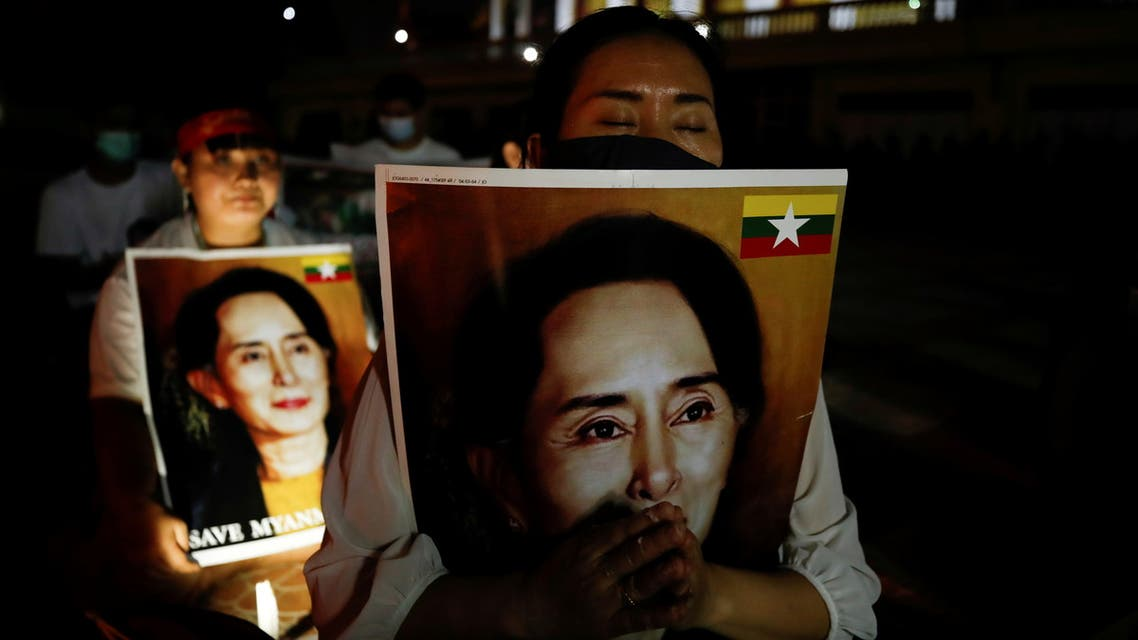 Migrants protesting against the military junta in Myanmar hold pictures of leader Aung San Suu Kyi, during a candlelight vigil at a Buddhist temple in Bangkok, Thailand, March 28, 2021. (Reuters)