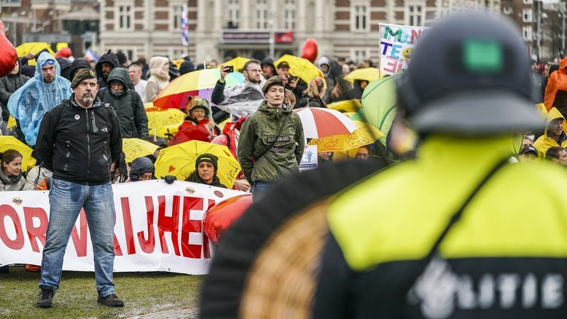 Dutch riot police watch campaigners in military clothing as they gather with protesters on the Museumplein for the so-called Coffee Drink campaign to denounce the government's handling of the COVID-19 pandemic, in Amsterdam on March 28, 2021. (Jeroen Jumelet/ANP/AFP)