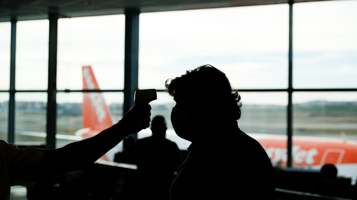A flight attendant checks the body temperature of a passenger at the entrance of a plane at Lisbon's airport during the coronavirus disease (COVID-19) outbreak, in Lisbon, Portugal June 15, 2020. REUTERS/Rafael Marchante