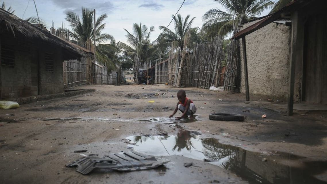 A child plays in one of the alleys of the port of Paquitequete near Pemba on March 29, 2021. (AFP)