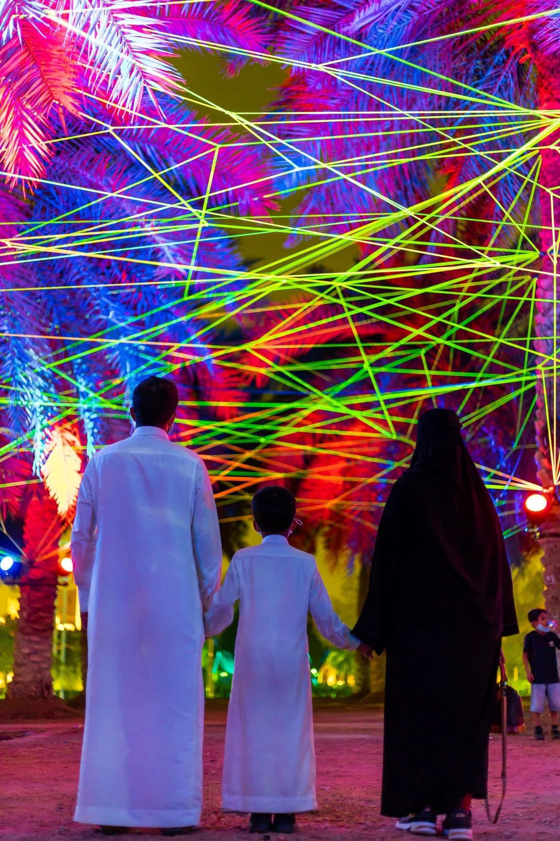 A Saudifamily enjoying Tom & Lien Dekyvere's 'Rhizome'  (2021) at the Palm Oasis in Riyadh. (Courtesy: Riyadh Art 2021)