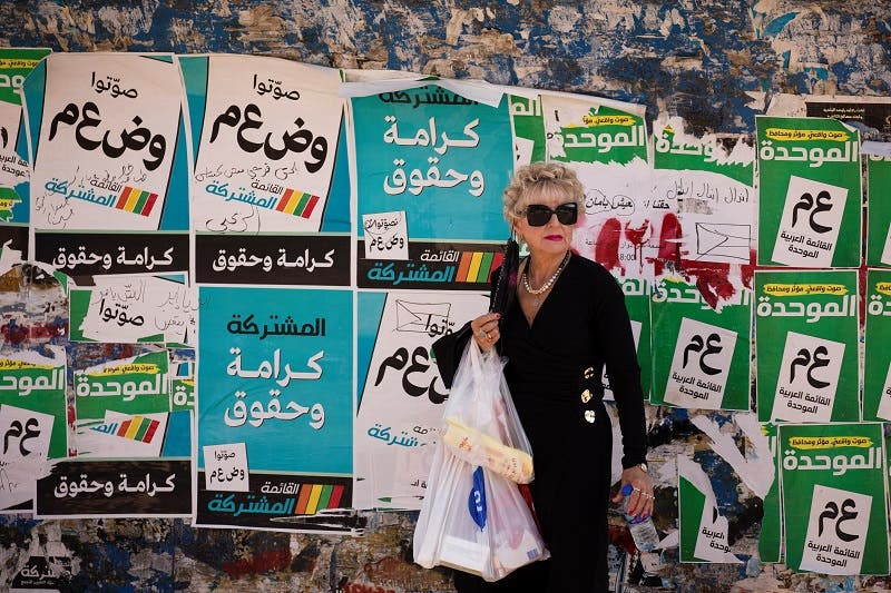 """A woman stands in front of """"Joint List"""" and """"Meretz"""" party election campaign posters ahead of the March 23 ballot in the northern Israeli-Arab city of Nazareth March 13, 2021. Picture taken March 13, 2021. (Reuters)"""