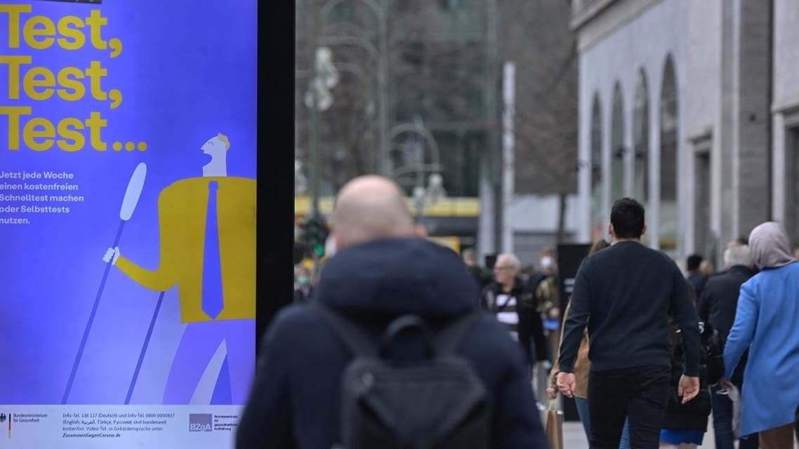 People walk past an ad promoting free coronavirus tests at Berlin's Kurfuerstendamm street on March 29, 2021, amid the novel coronavirus pandemic. (AFP)