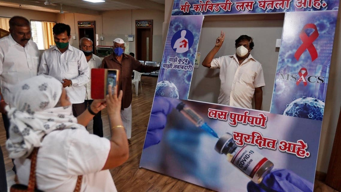 """A man poses behind a cardboard cut-out with the words """"I have taken the vaccine, it's completely safe"""" after receiving a dose of COVISHIELD coronavirus vaccine manufactured by Serum Institute of India, at a hospital in Satara district in the western state of Maharashtra, India, on March 24, 2021. (Reuters)"""