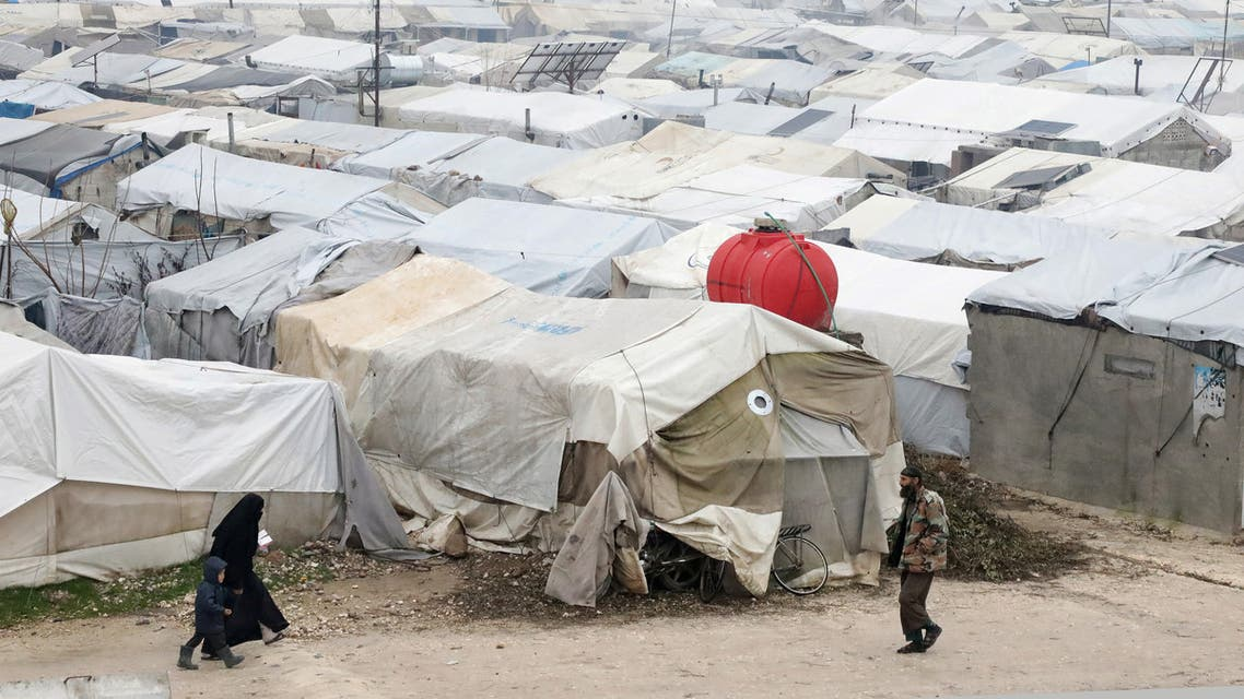 FILE PHOTO: Internally displaced Syrian woman walks with a child, near tents at a camp in Northern Aleppo countryside, Syria January 20, 2021. Picture taken January 20, 2021. REUTERS/Mahmoud Hassano/File Photo