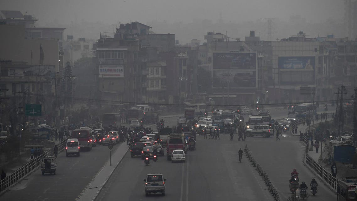 Commuters make their way along a road amid smoggy conditions in Kathmandu on March 29, 2021. (AFP)