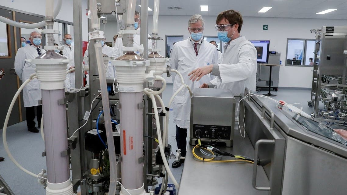 Belgian King Philippe listens the explanations on LNP (Lipid Nano Particle) SKID machine during a visit to a factory producing the Pfizer-BioNTech COVID-19 vaccine in the town of Puurs, Belgium, on March 30, 2021. (Reuters)