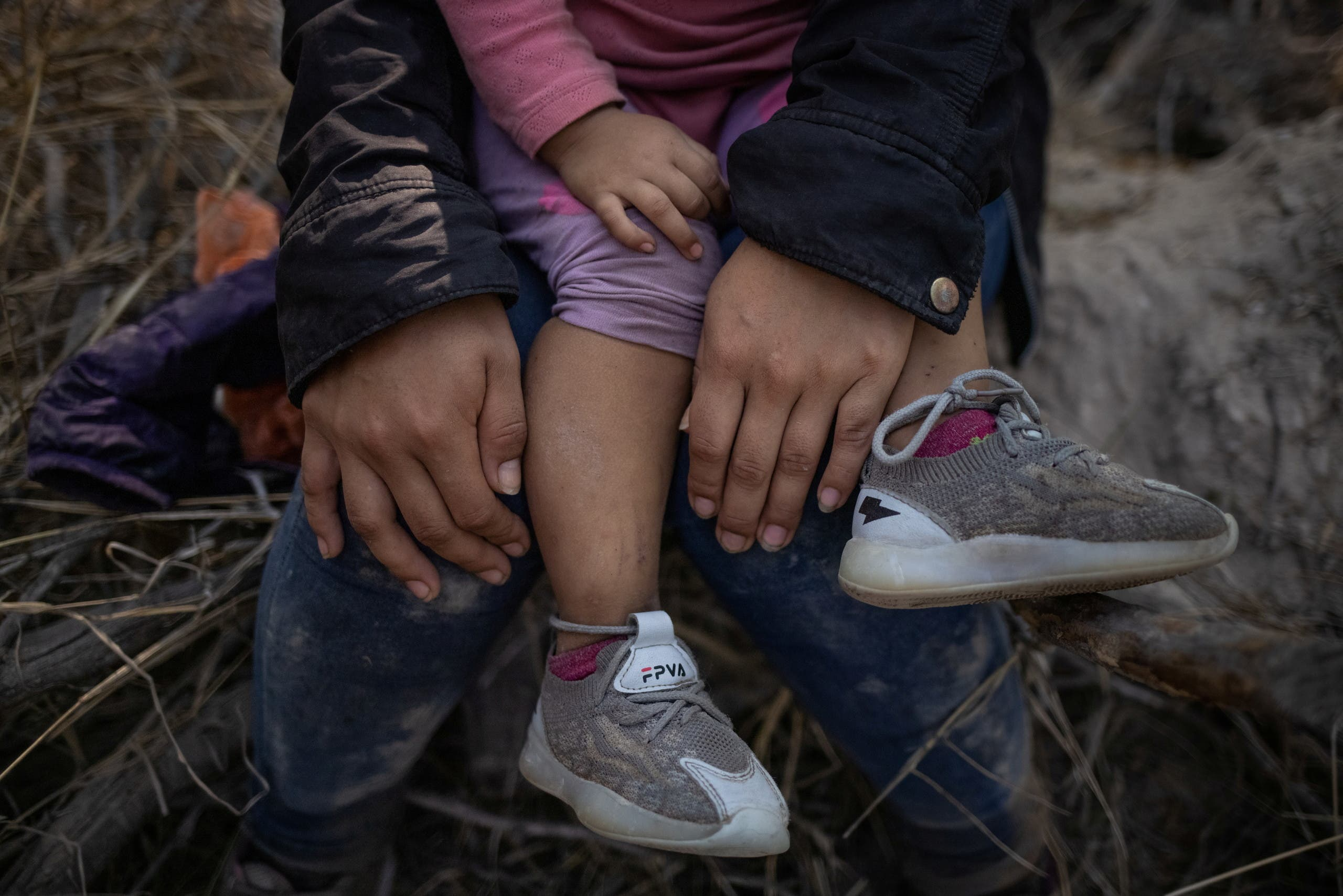 An asylum seeking migrant from Central America holds his child after a group of 107 crossed the Rio Grande river into the United States from Mexico on rafts in Penitas, Texas, U.S., March 26, 2021. Picture taken March 26, 2021. (Reuters)