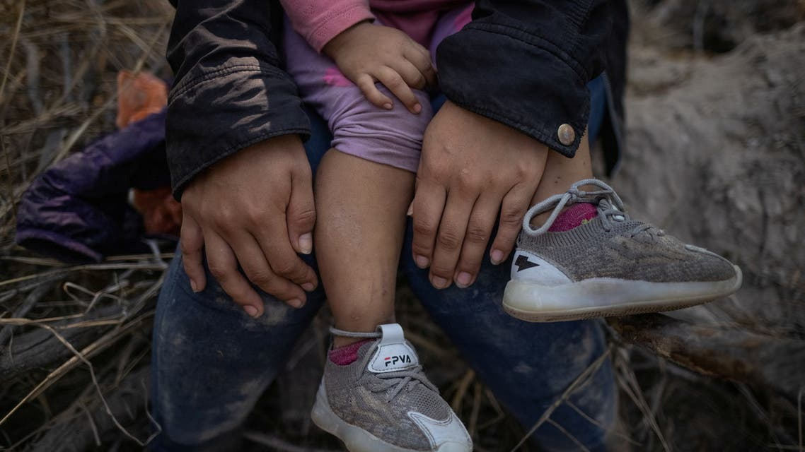 An asylum seeking migrant from Central America holds his child after a group of 107 crossed the Rio Grande river into the United States from Mexico on rafts in Penitas, Texas, U.S., March 26, 2021. Picture taken March 26, 2021. REUTERS/Adrees Latif