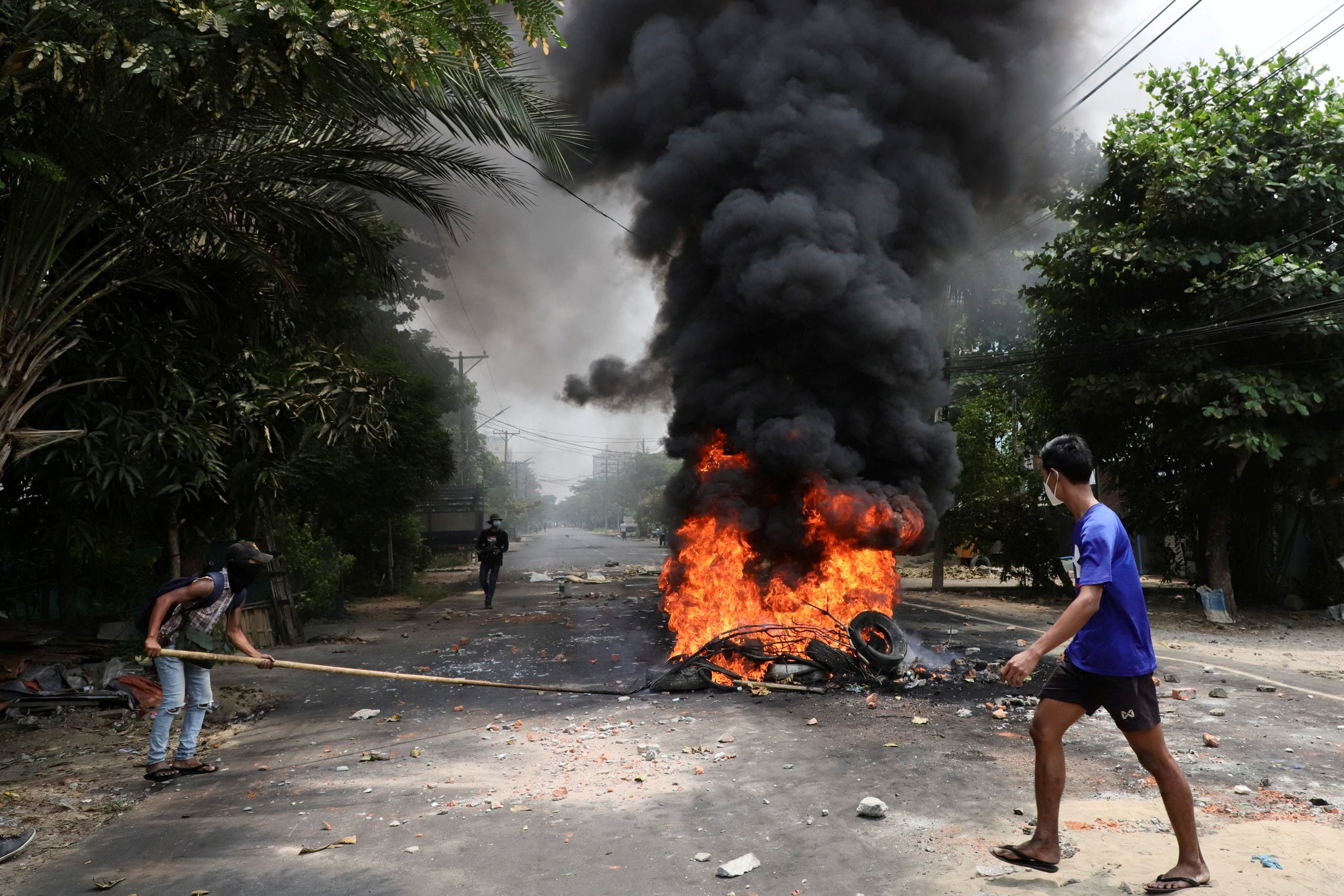 An anti-coup protester walks past burning tires after activists launched a garbage strike against the military rule, in Yangon, Myanmar March 30, 2021. (File photo: Reuters)