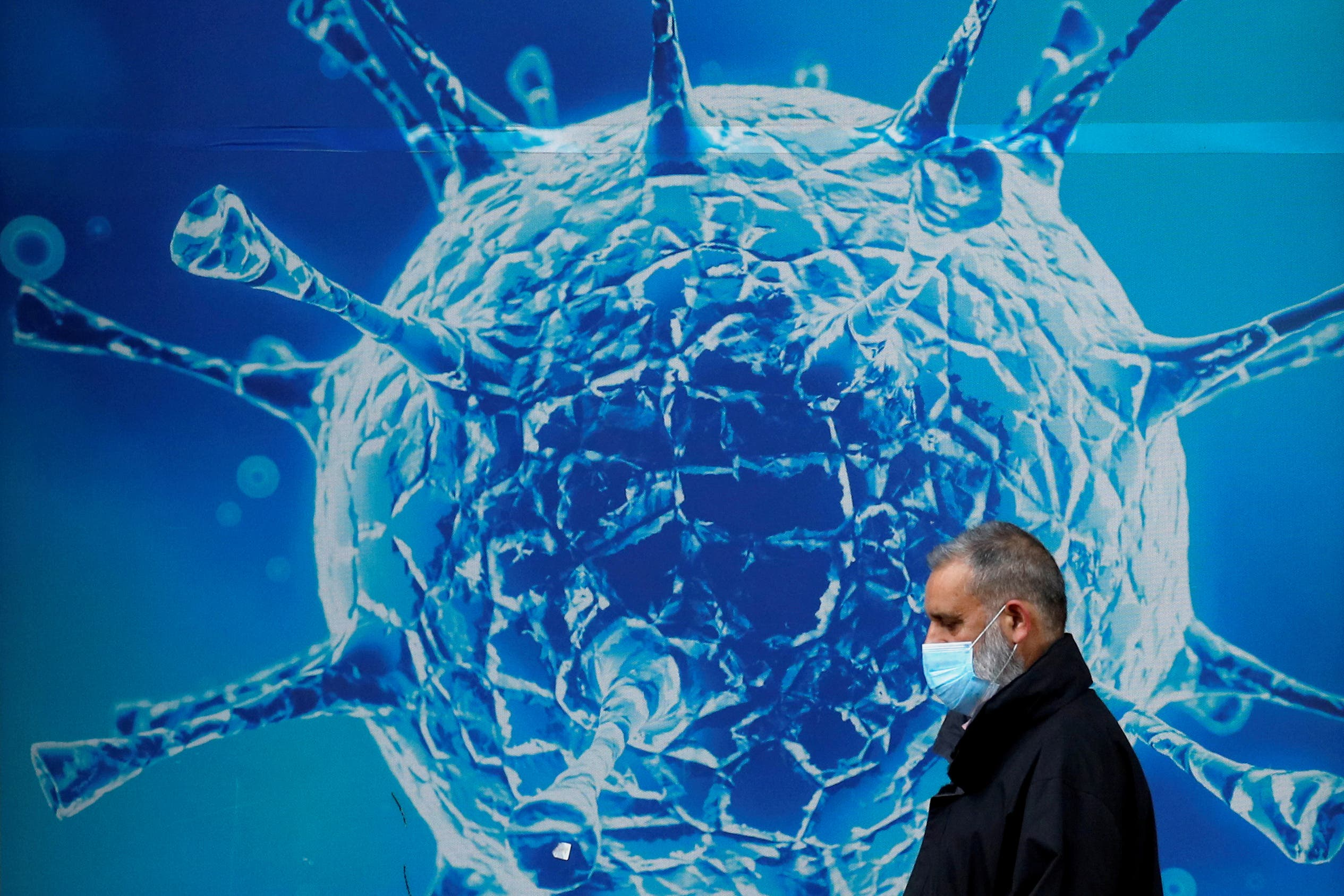 A man wearing a protective face mask walks past an illustration of a virus outside a regional science centre in Oldham, Britain August 3, 2020. (File photo: Reuters)