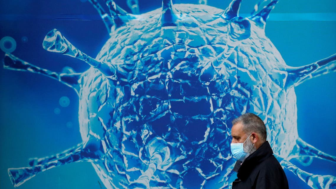FILE PHOTO: A man wearing a protective face mask walks past an illustration of a virus outside a regional science centre in Oldham, Britain August 3, 2020. (File photo: Reuters)