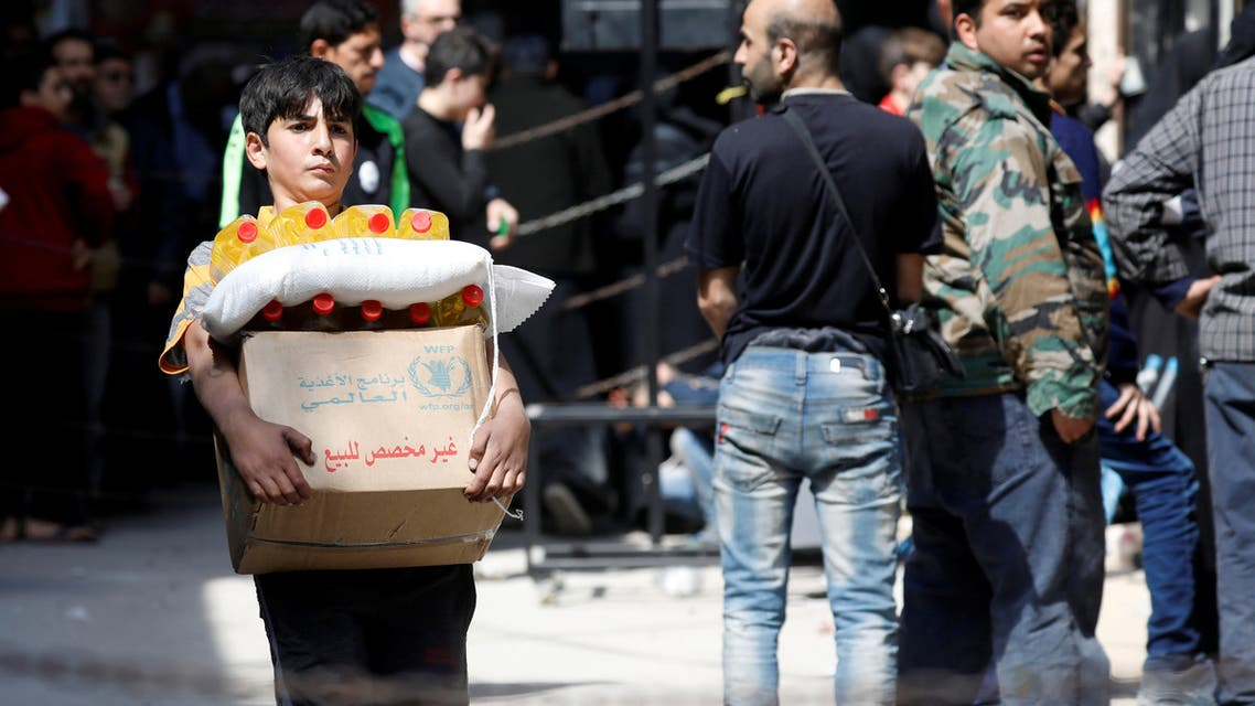 A boy holds a cardboard box of food aid received from World Food Programme in Aleppo's Kalasa district, Syria April 10, 2019. Picture taken April 10, 2019. REUTERS/Omar Sanadiki