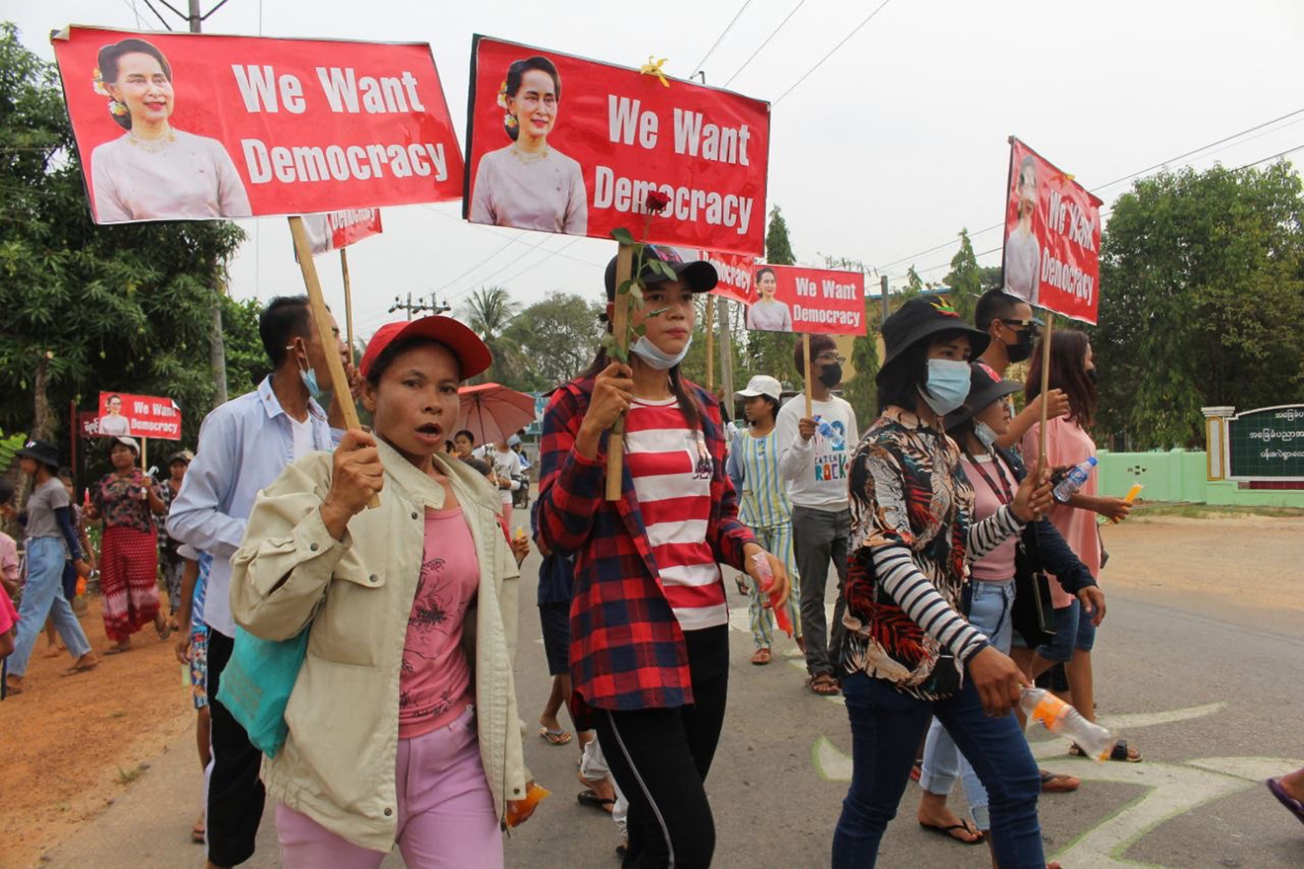 This handout photo taken and released by Dawei Watch on March 30, 2021 shows protesters holding signs with portraits of detained Myanmar civilian leader Aung San Suu Kyi during a demonstration against the military coup in Launglon township in Dawei.
