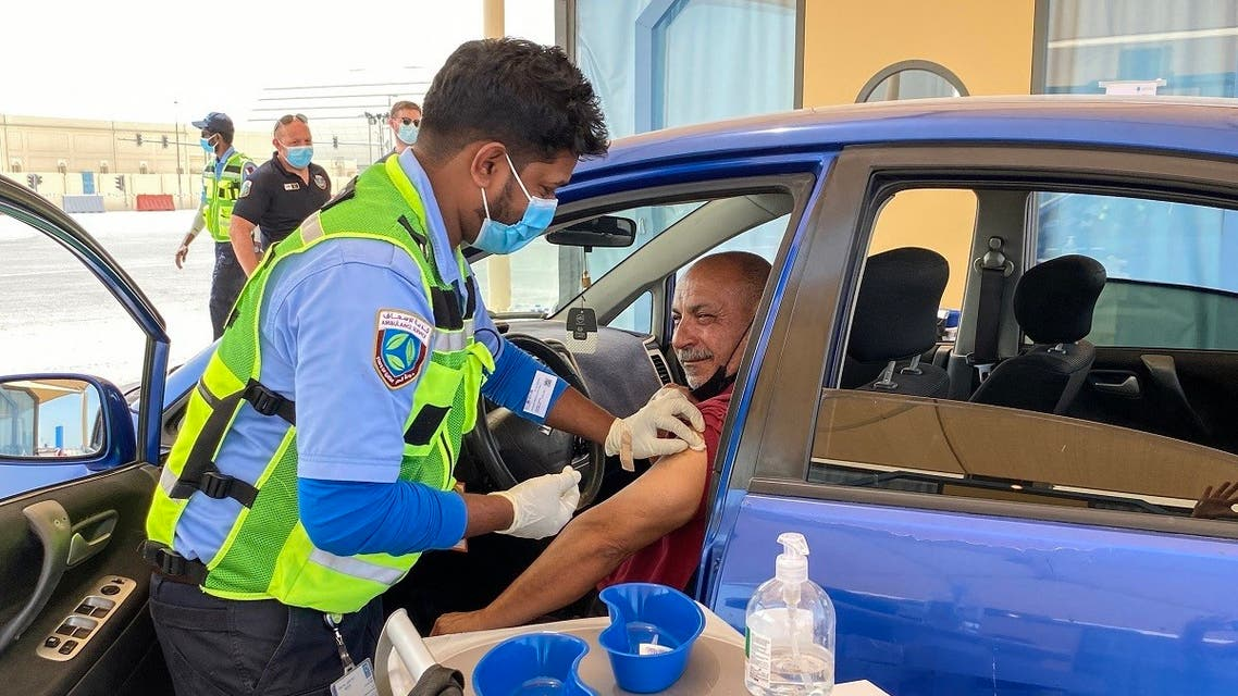A health worker inoculates a man against the coronavirus at a drive-through vaccination centre in the city of al-Wakrah, north of the capital Doha, on March 31, 2021. (AFP)