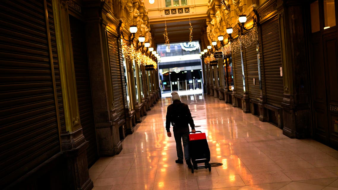 A man pulls a trolley next to closed shops in a commercial street during a partial lockdown due to the coronavirus COVID-19 in downtown Brussels, Friday, Nov. 20, 2020. (AP)