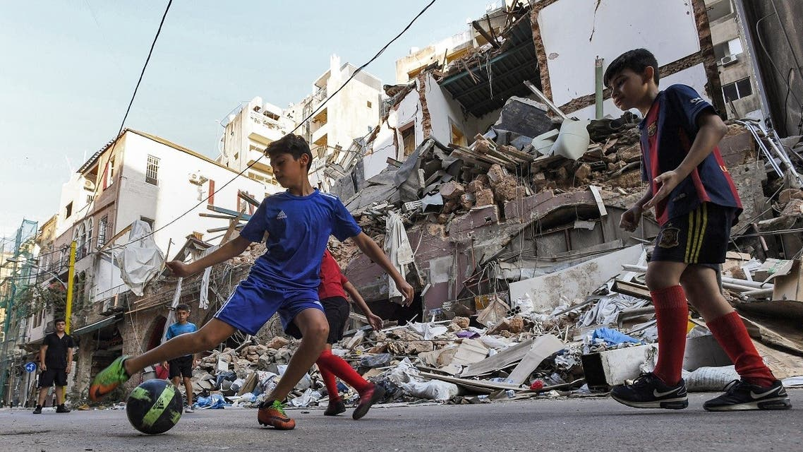Children play with a football past rubble and destruction along a street in the Gemmayzeh district of Lebanon's capital Beirut on August 28, 2020. (AFP)