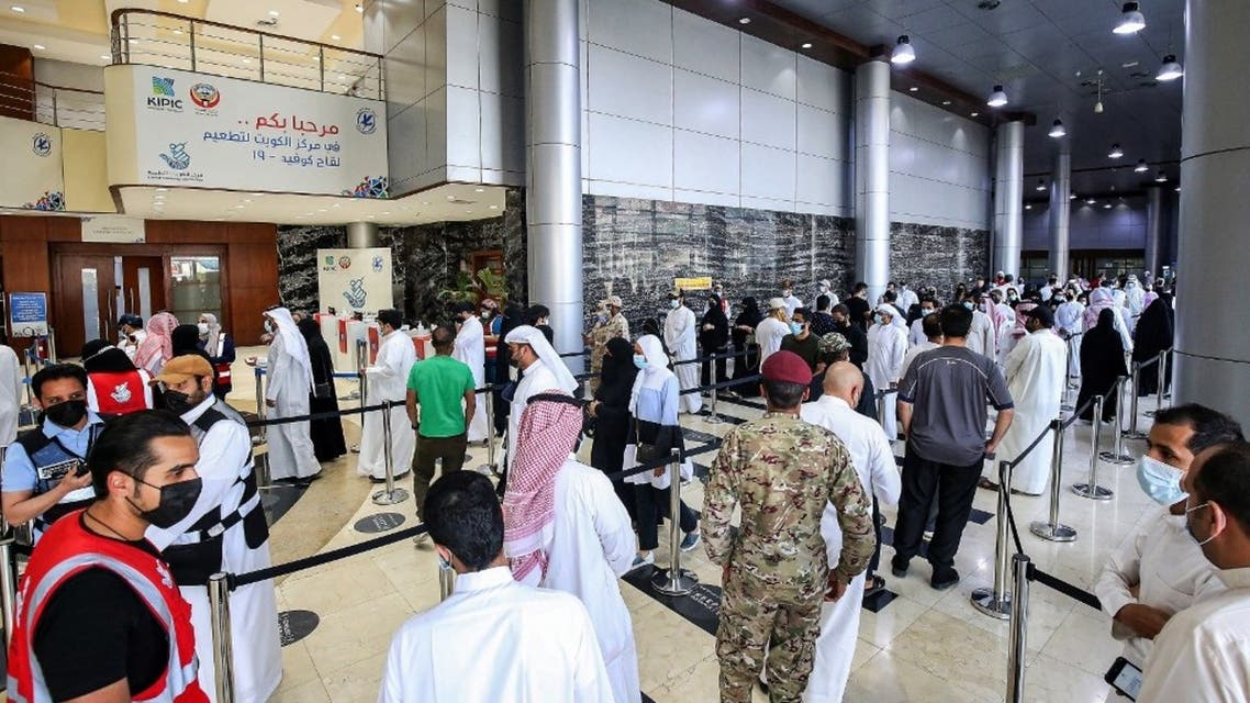 People queue as they wait their turn to receive a dose of COVID-19 coronavirus vaccine at the make-shift vaccination centre at the Kuwait International Fairground in the Mishref suburb south of Kuwait City on March 21, 2021. (AFP)