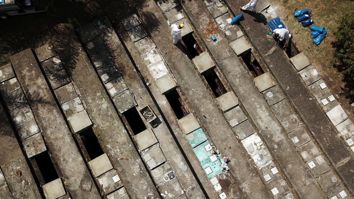 Aerial view of gravediggers wearing protective suits as they perform exhumations to open space on cement graves as new burials are suspended, except private deposits and children, at Vila Nova Cachoeirinha cemetery amid the outbreak of the coronavirus disease (COVID-19) in Sao Paulo, Brazil, April 1, 2021. (Reuters)