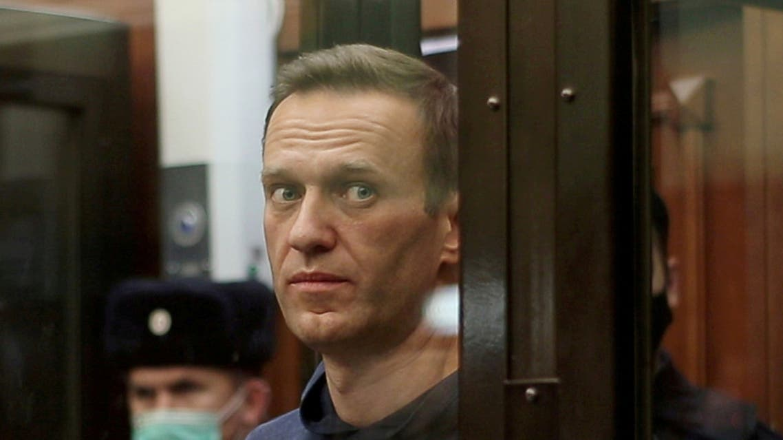 A still image taken from video footage shows Russian opposition leader Alexei Navalny, who is accused of flouting the terms of a suspended sentence for embezzlement, inside a defendant dock during the announcement of a court verdict in Moscow, Russia February 2, 2021. (Reuters)