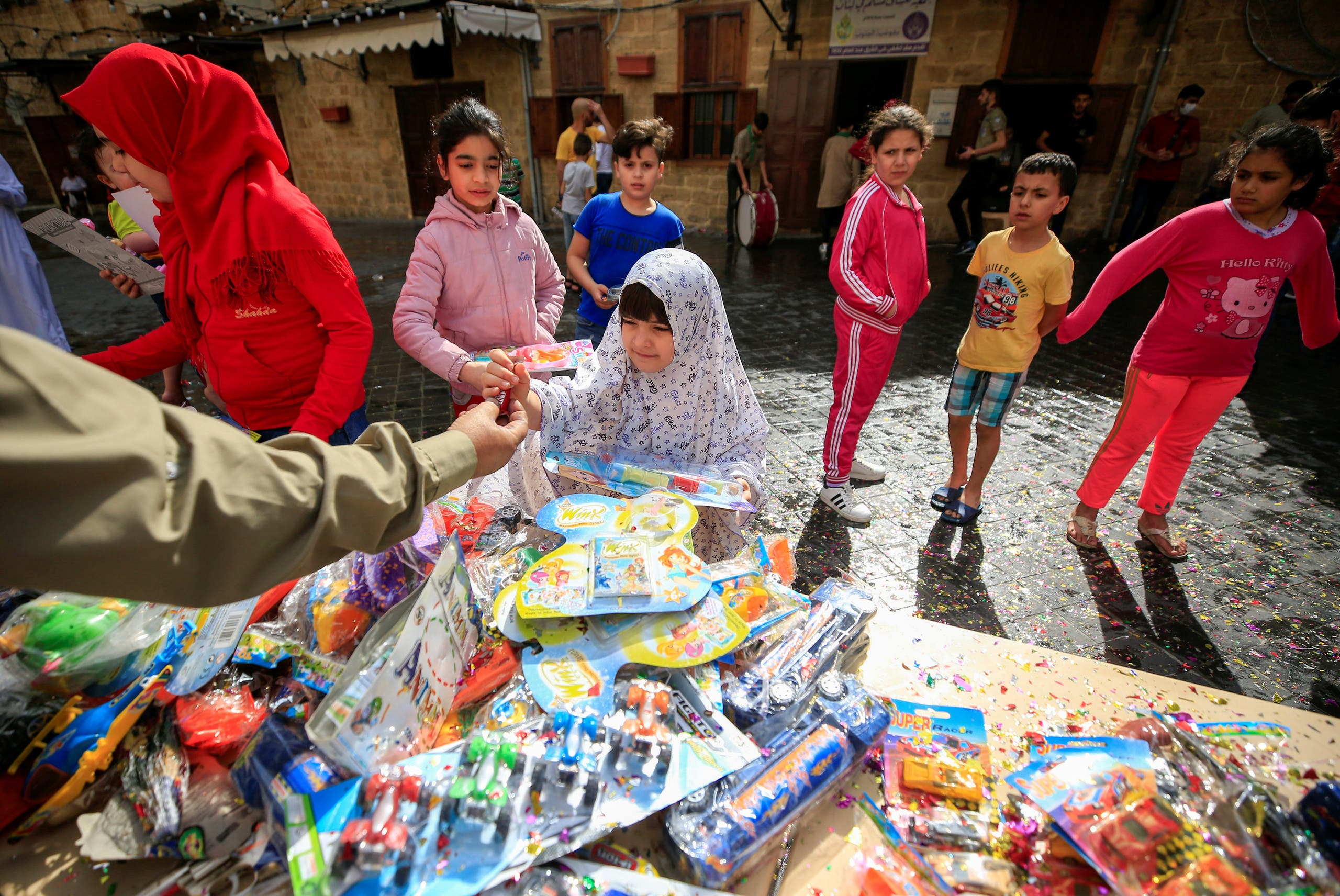 Children receive toys at a gift-giving event, on the first day of the Muslim holiday of Eid al-Fitr, amid concerns over the spread of the coronavirus disease (COVID-19), in the port city of Sidon, southern Lebanon, May 24, 2020. (Reuters)