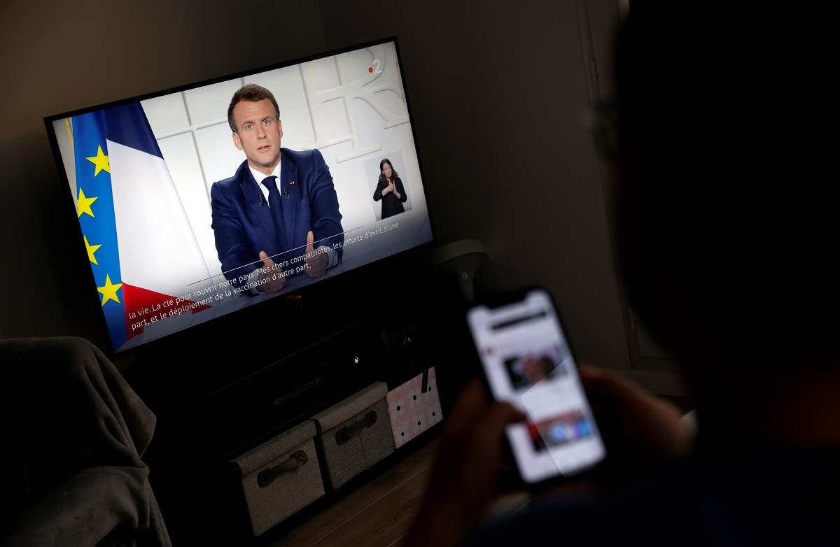 A man watches French President Emmanuel Macron on a TV screen, at his home in Saint-Sebastien-sur-Loire as Macron addresses the nation about the state of the coronavirus disease (COVID-19) outbreak as a fast-spreading third wave of COVID-19 infections threatens to over-run hospitals in France. (Reuters)