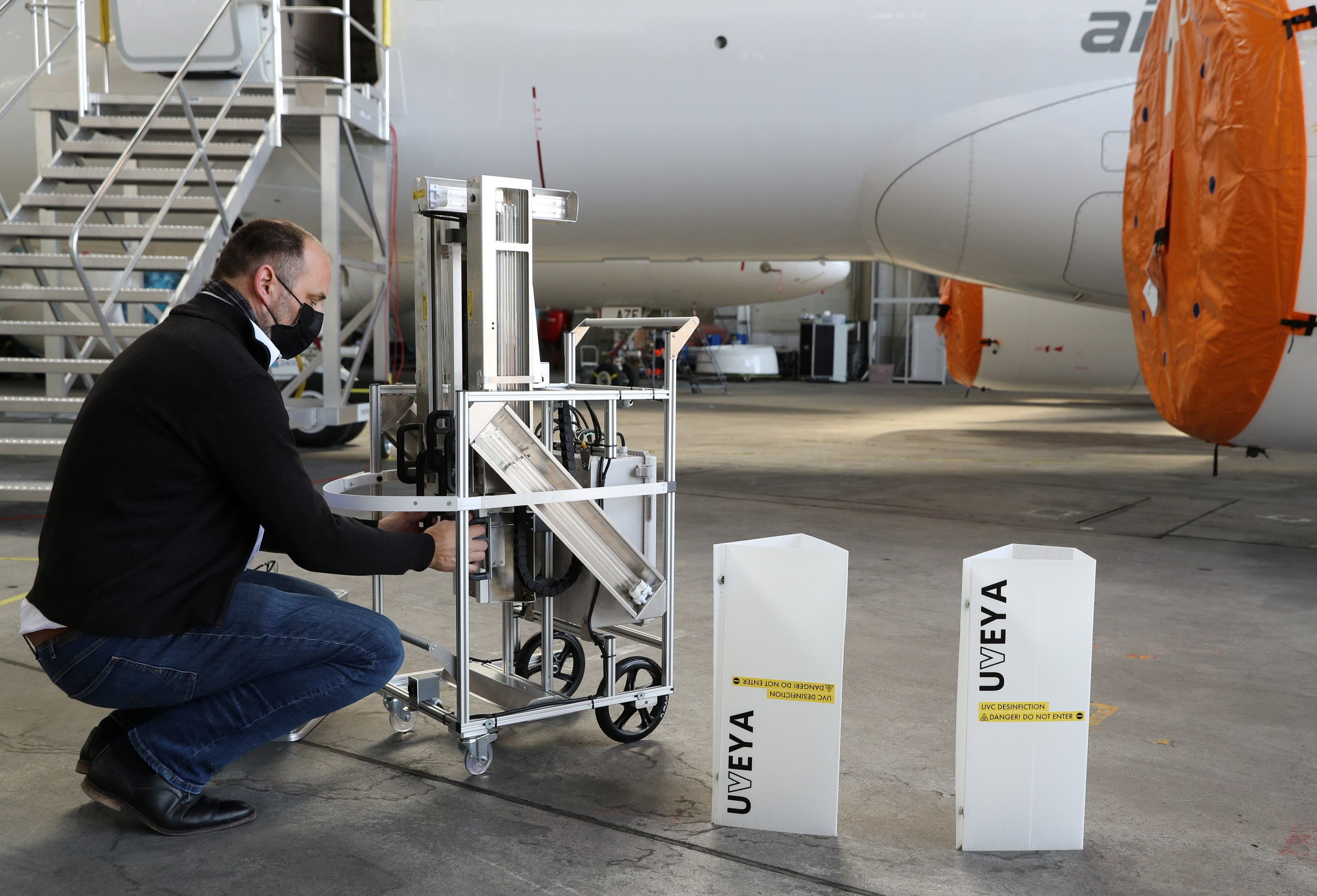 Elmiger of Swiss company UVeya disassembles a robot armed with virus-killing ultraviolet light at Zurich Airport. (Reuters)